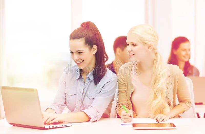 Σπουδαστές με το lap-top, το PC ταμπλετών και τα σημειωματάρια στοκ εικόνες
