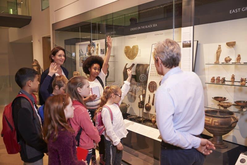 Σπουδαστές που εξετάζουν τα χειροποίητα αντικείμενα σε περίπτωση που στο ταξίδι στο μουσείο στοκ φωτογραφία με δικαίωμα ελεύθερης χρήσης