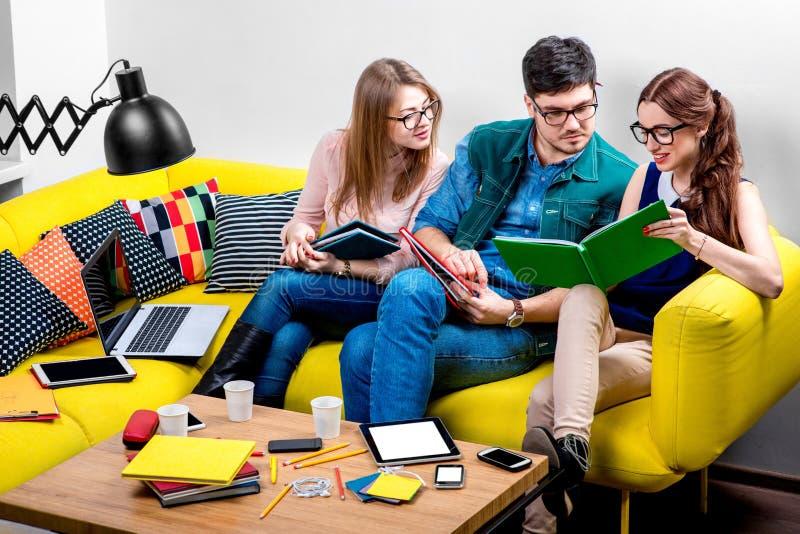 Σπουδαστές που εργάζονται στον καναπέ στοκ εικόνες με δικαίωμα ελεύθερης χρήσης