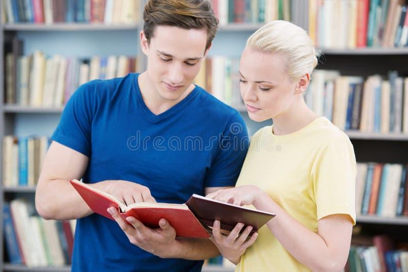 Σπουδαστές που διαβάζουν τα βιβλία στη βιβλιοθήκη στοκ εικόνες