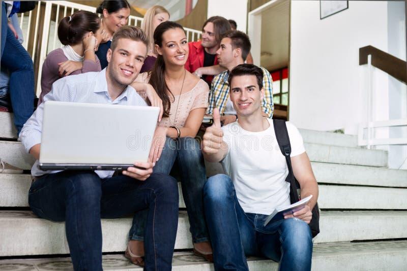 Σπουδαστές που κάθονται στα βήματα στο κολλέγιο στοκ φωτογραφίες