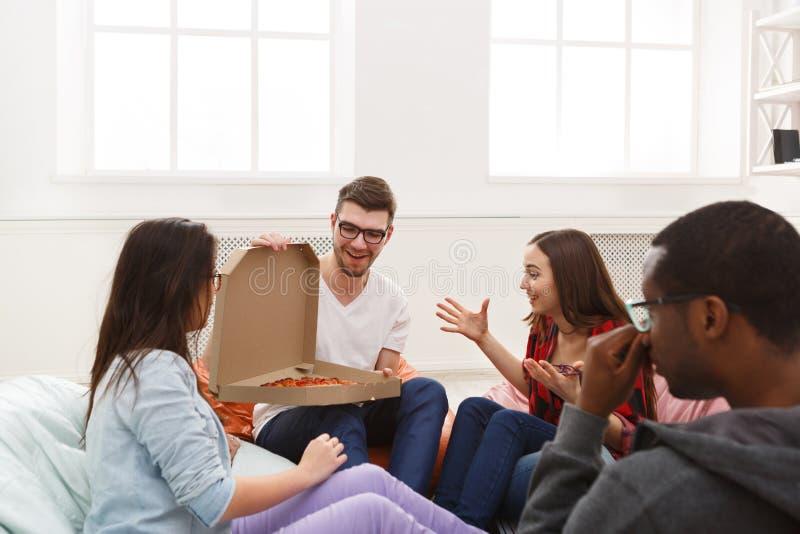 Σπουδαστές που μοιράζονται το κόμμα πιτσών στο σπίτι στοκ φωτογραφίες με δικαίωμα ελεύθερης χρήσης