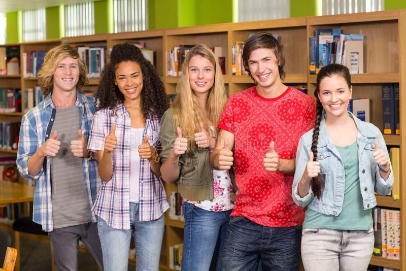 Σπουδαστές που οι αντίχειρες επάνω στη βιβλιοθήκη στοκ εικόνα με δικαίωμα ελεύθερης χρήσης