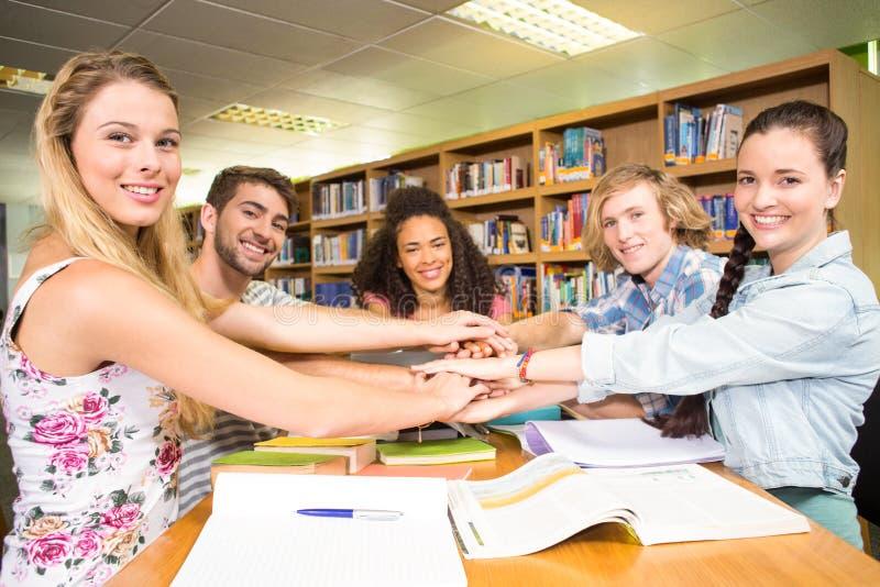 Σπουδαστές που τοποθετούν τα χέρια μαζί πέρα από τον πίνακα βιβλιοθηκών στοκ φωτογραφία με δικαίωμα ελεύθερης χρήσης