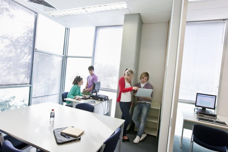Σπουδαστές που χρησιμοποιούν τους υπολογιστές στοκ φωτογραφία