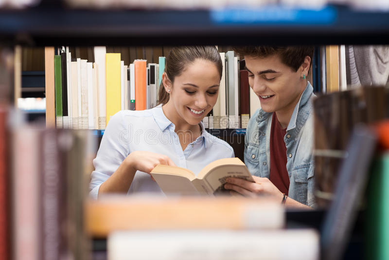 Σπουδαστές που ψάχνουν για τα βιβλία στη βιβλιοθήκη στοκ εικόνες