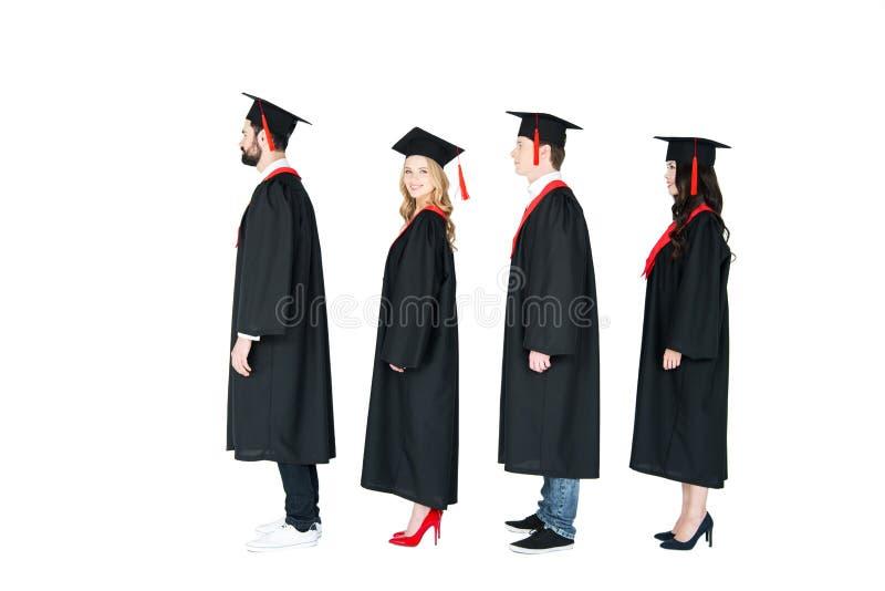 Σπουδαστές στα ακαδημαϊκά καλύμματα και εσθήτες βαθμολόγησης που στέκονται σε μια σειρά στοκ εικόνα