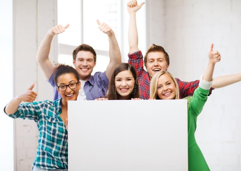 Σπουδαστές στο σχολείο με τον κενό λευκό πίνακα στοκ εικόνες
