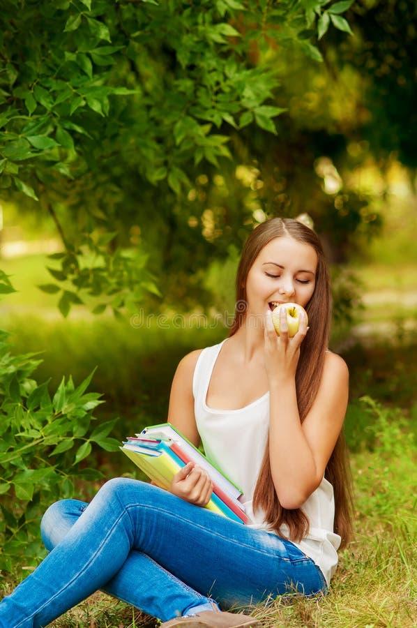 Σπουδαστής κοριτσιών με τα βιβλία που τρώει ένα μήλο στοκ φωτογραφία