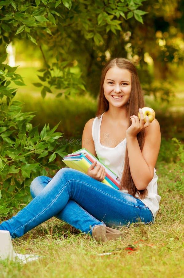 Σπουδαστής κοριτσιών με τα βιβλία που τρώει ένα μήλο στοκ φωτογραφία με δικαίωμα ελεύθερης χρήσης