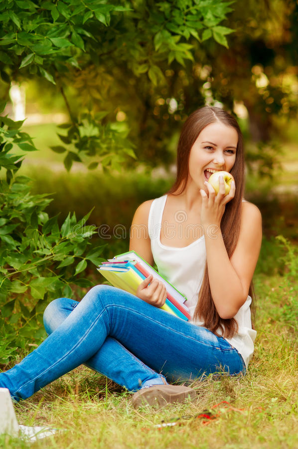 Σπουδαστής κοριτσιών με τα βιβλία που τρώει ένα μήλο στοκ εικόνες