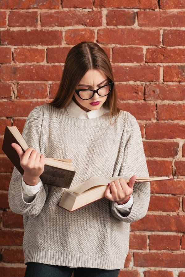 Σπουδαστής κοριτσιών που διαβάζει την κινηματογράφηση σε πρώτο πλάνο δύο βιβλίων parallelly στοκ εικόνα