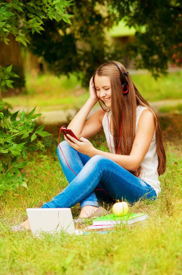 Σπουδαστής κοριτσιών στη χλόη στα ακουστικά με το τηλέφωνο στοκ εικόνα