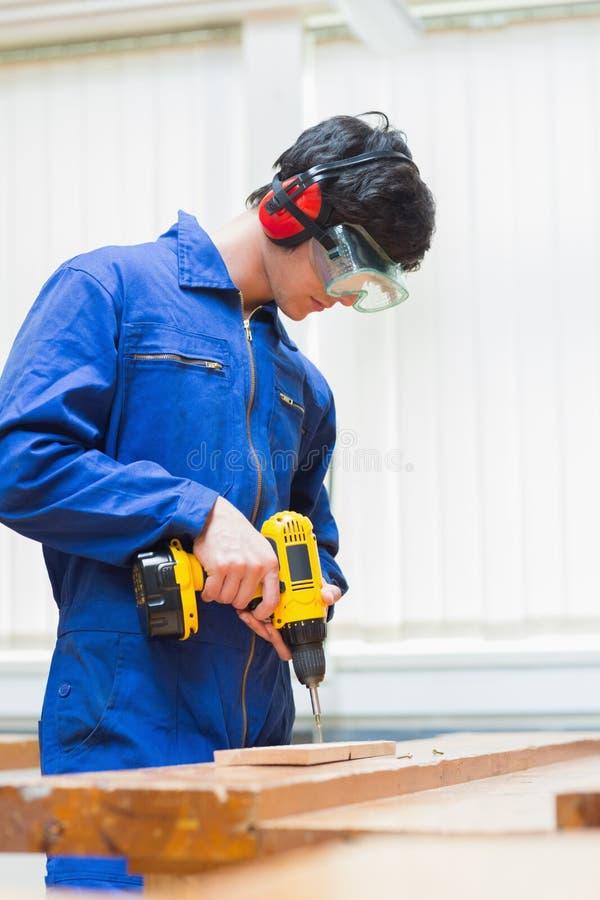 Σπουδαστής μιας κατηγορίας ξυλουργικής που τρυπά μια τρύπα με τρυπάνι στοκ φωτογραφία