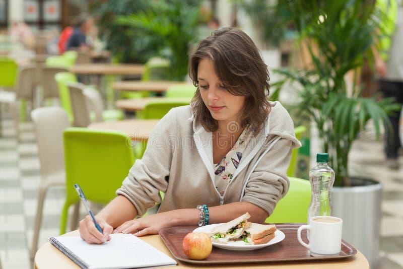 Σπουδαστής που κάνει την εργασία ενώ έχοντας το πρόγευμα στον καφέ στοκ φωτογραφία