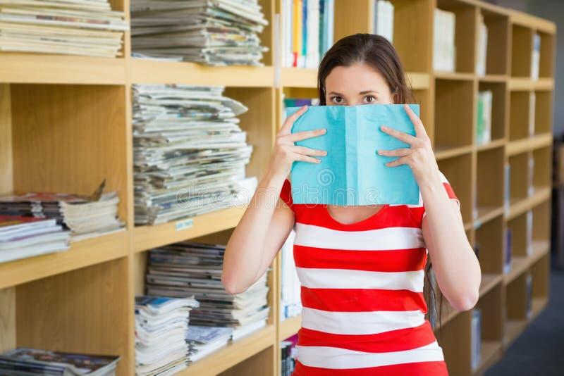 Σπουδαστής που καλύπτει το πρόσωπο με το βιβλίο στη βιβλιοθήκη στοκ εικόνες