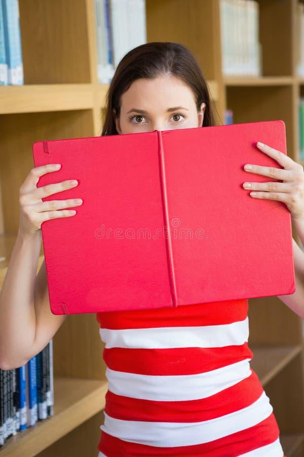 Σπουδαστής που καλύπτει το πρόσωπο με το βιβλίο στη βιβλιοθήκη στοκ φωτογραφία με δικαίωμα ελεύθερης χρήσης