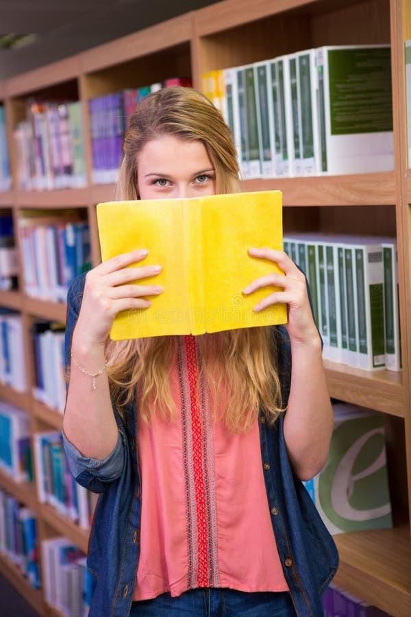 Σπουδαστής που καλύπτει το πρόσωπο με το βιβλίο στη βιβλιοθήκη στοκ φωτογραφία