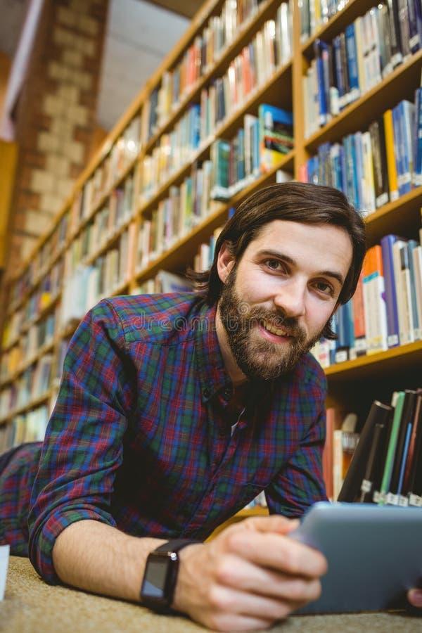 Σπουδαστής που μελετά στο πάτωμα στη βιβλιοθήκη που φορά το έξυπνο ρολόι στοκ εικόνες με δικαίωμα ελεύθερης χρήσης