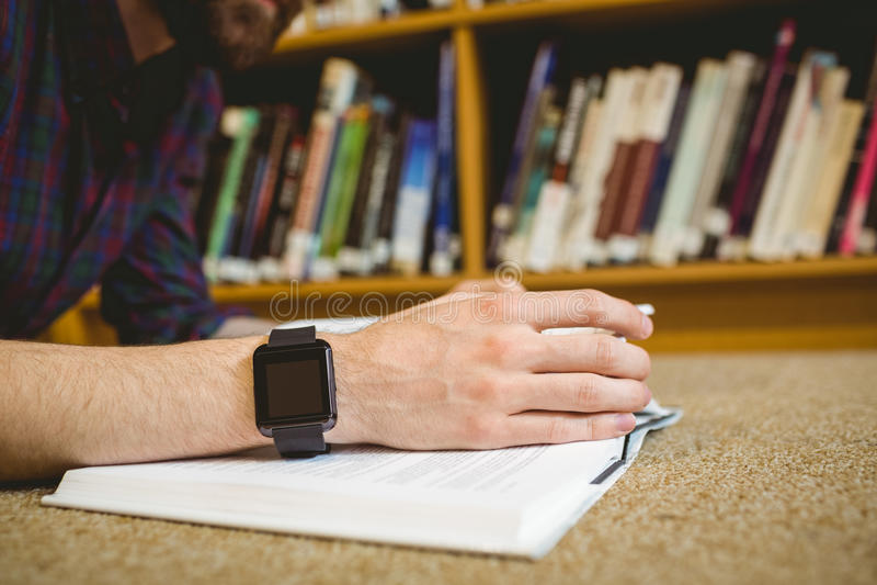 Σπουδαστής που μελετά στο πάτωμα στη βιβλιοθήκη που φορά το έξυπνο ρολόι στοκ φωτογραφίες