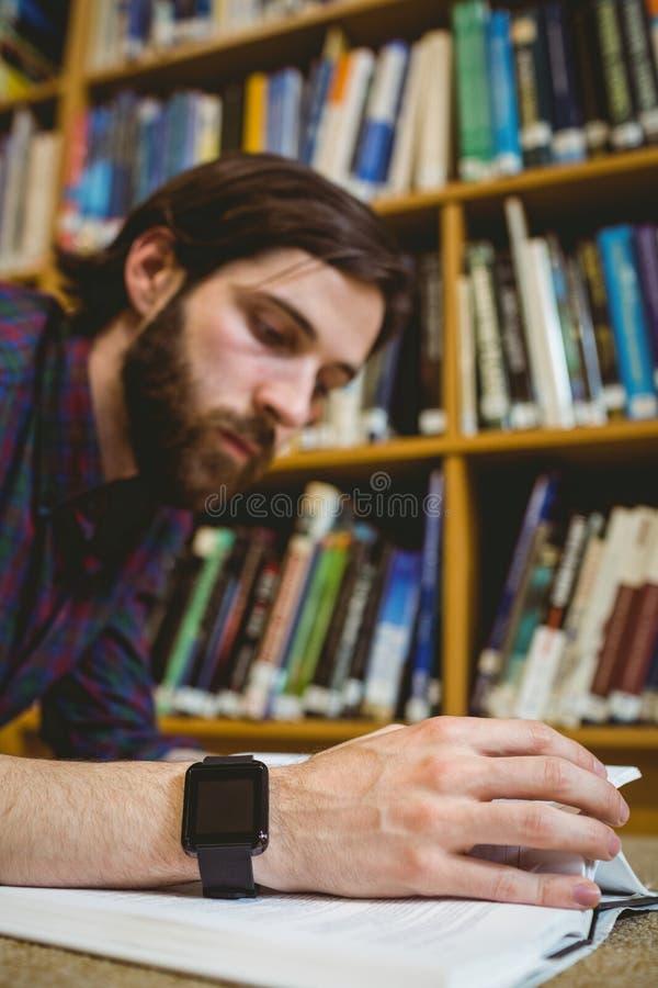 Σπουδαστής που μελετά στο πάτωμα στη βιβλιοθήκη που φορά το έξυπνο ρολόι στοκ φωτογραφία