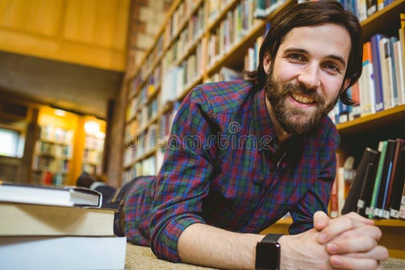 Σπουδαστής που μελετά στο πάτωμα στη βιβλιοθήκη που φορά το έξυπνο ρολόι στοκ φωτογραφίες με δικαίωμα ελεύθερης χρήσης