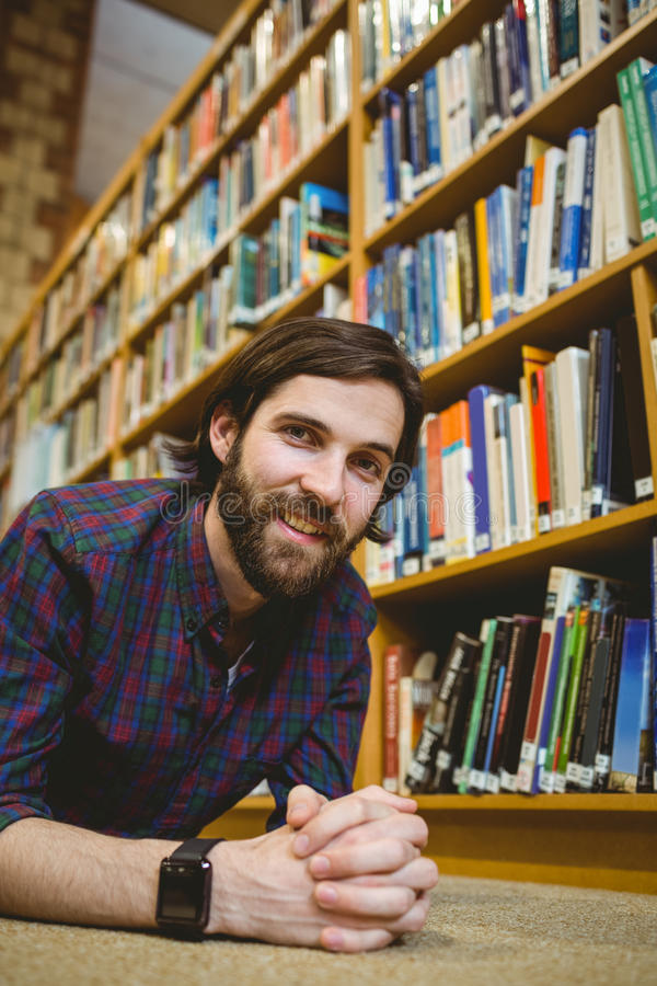 Σπουδαστής που χαμογελά στο πάτωμα στη βιβλιοθήκη που φορά το έξυπνο ρολόι στοκ φωτογραφία