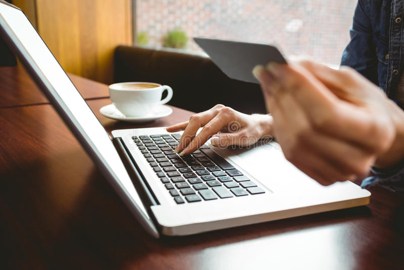 Σπουδαστής που χρησιμοποιεί το lap-top στον καφέ για να ψωνίσει on-line στοκ φωτογραφία