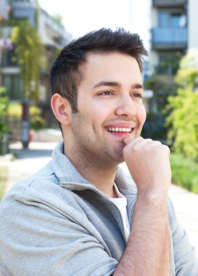 Σπουδαστής σε ένα γκρίζο σακάκι που ονειρεύεται υπαίθρια σε ένα SU στοκ εικόνα με δικαίωμα ελεύθερης χρήσης