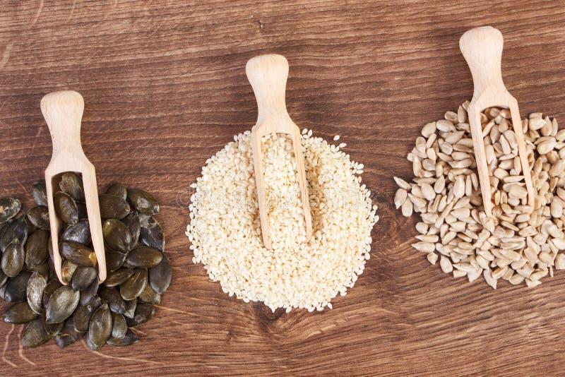 Σπόροι ηλίανθων, κολοκύθας και σουσαμιού με την ξύλινη σέσουλα εν πλω, υγιής έννοια διατροφής στοκ εικόνες με δικαίωμα ελεύθερης χρήσης