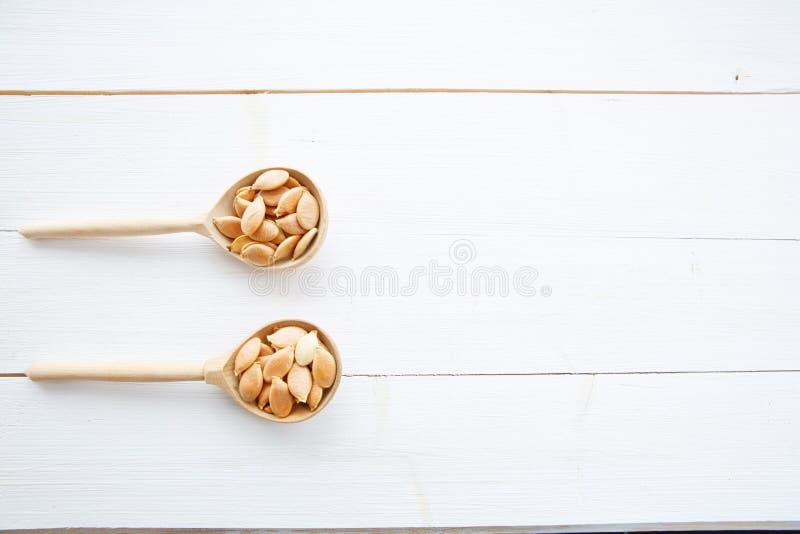 Σπόροι κολοκύθας στο κουτάλι στον άσπρο ξύλινο πίνακα στοκ εικόνες