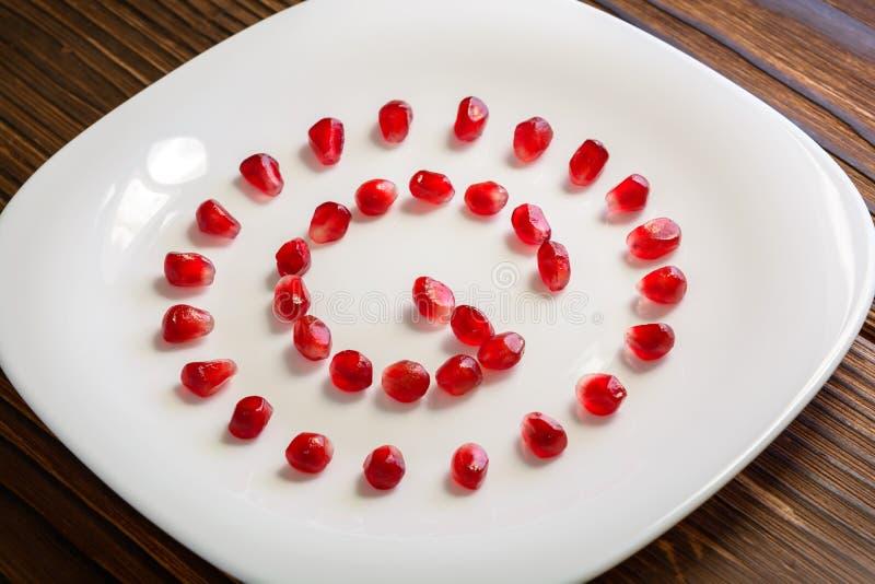 Σπόροι ροδιών με μορφή γράμματος Γ στο άσπρο πιάτο στο αγροτικό W στοκ φωτογραφία