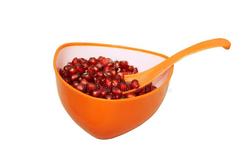 Σπόροι ροδιών στο πορτοκαλί φλυτζάνι με το κουτάλι στοκ εικόνες