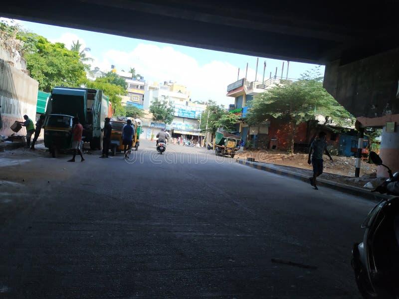 Στάθμευση του φορτηγού μεταφοράς σκουπιδιών και του αυτοκινήτου Rickshaw κάτω από τη γέφυρα Laggere στοκ φωτογραφία
