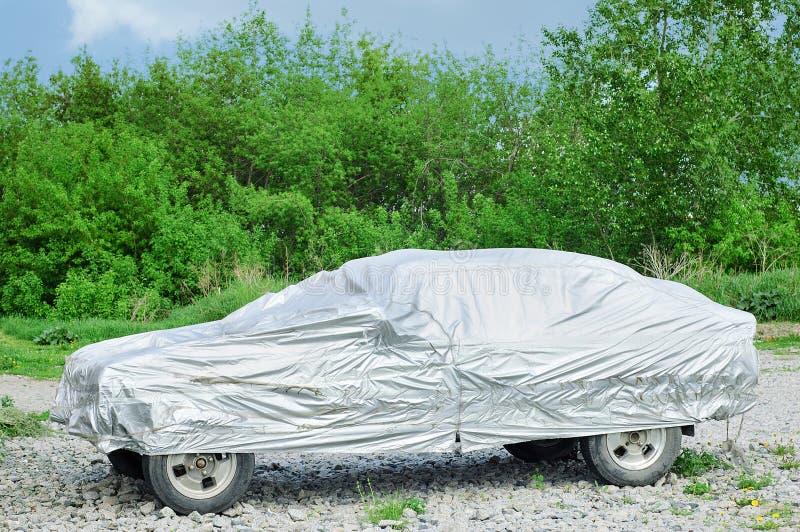 Στάσεις αυτοκινήτων στο αμμοχάλικο στην κάλυψη για το αυτοκίνητο Στα πλαίσια των πράσινων δέντρων στοκ εικόνες