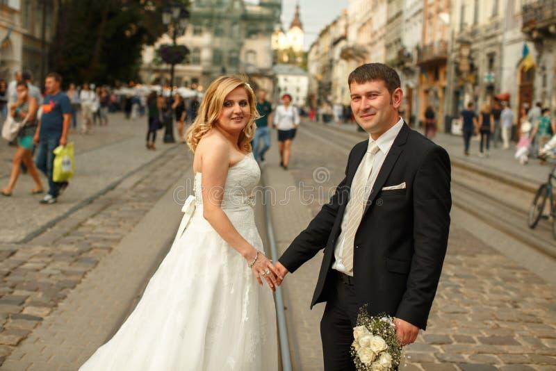 Στάσεις γαμήλιων ζευγών στις τροχιοδρομικές γραμμές κάπου σε ένα παλαιό μέρος ο στοκ φωτογραφία με δικαίωμα ελεύθερης χρήσης