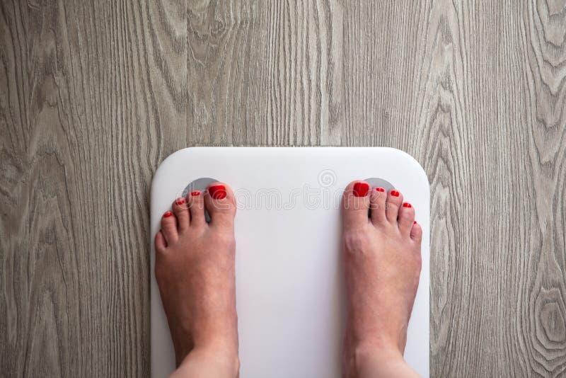 Στάσεις γυναικών στις άσπρες σύγχρονες ηλεκτρονικές κλίμακες αισθητήρων Μόνο τα πόδια είναι ορατά Στάση κλιμάκων στο γκρίζο ξύλιν στοκ εικόνα