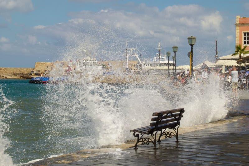 Στάσεις κενές πάγκων στην άκρη του αναχώματος Chania για το οποίο τα κύματα και πολλοί παφλασμοί κτυπούν στοκ εικόνα