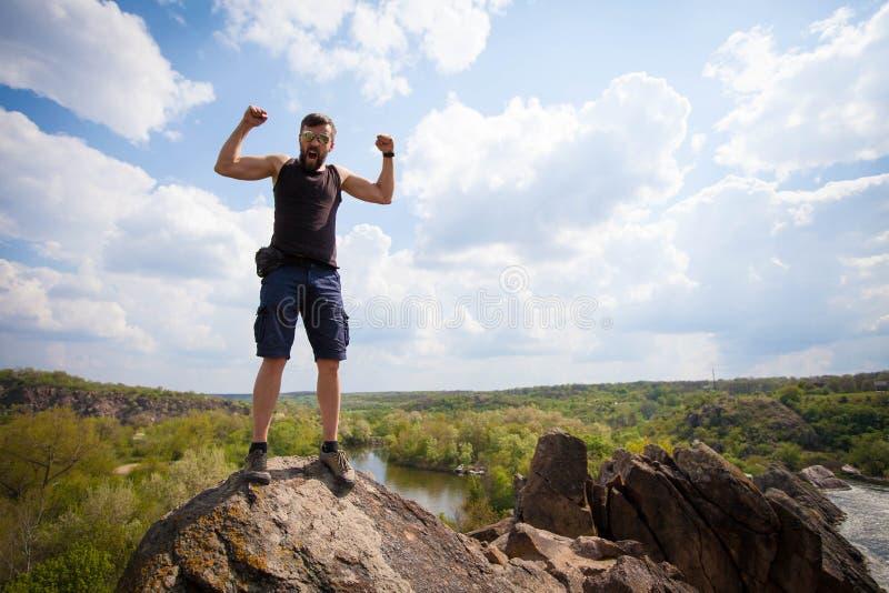 Στάσεις νεαρών άνδρων στην κορυφή του βράχου στοκ φωτογραφίες με δικαίωμα ελεύθερης χρήσης