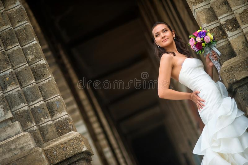 Στάσεις νυφών στον τοίχο πετρών σε ένα όμορφο άσπρο γαμήλιο φόρεμα στοκ εικόνα