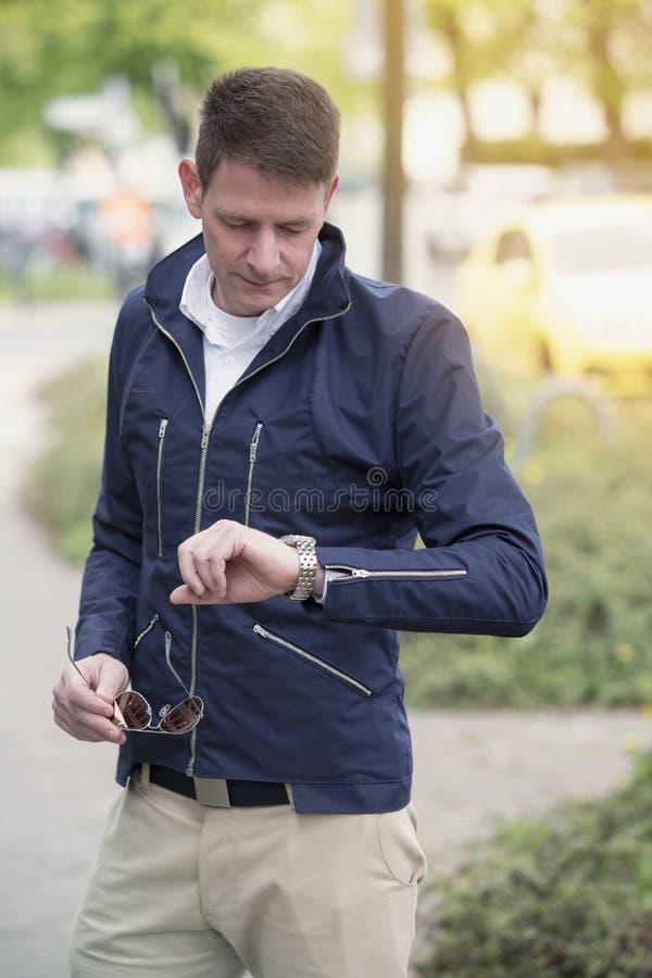 Στάση ατόμων εξωτερική και εξέταση το ρολόι του στοκ φωτογραφία με δικαίωμα ελεύθερης χρήσης