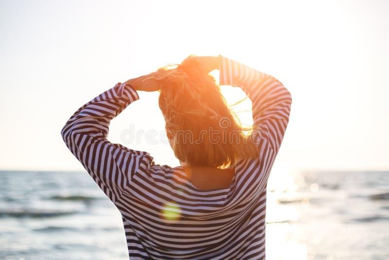 Στάση γυναικών που εξετάζει την κινηματογράφηση σε πρώτο πλάνο θάλασσας στον ήλιο στοκ εικόνα