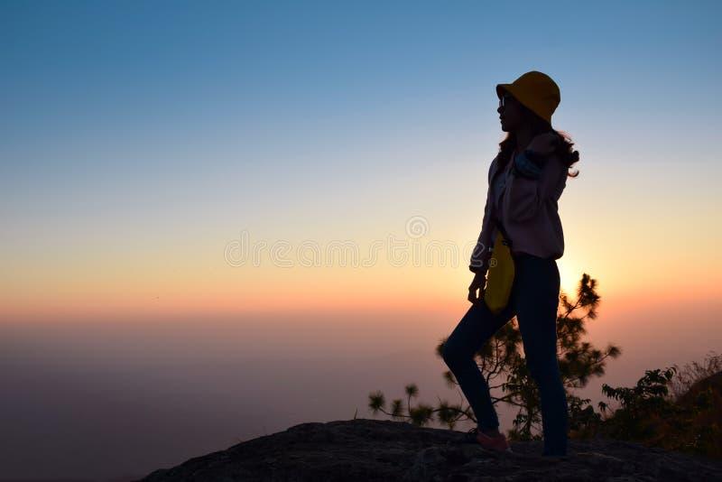 Στάση γυναικών σκιαγραφιών στο βουνό με το ηλιοβασίλεμα στοκ φωτογραφίες