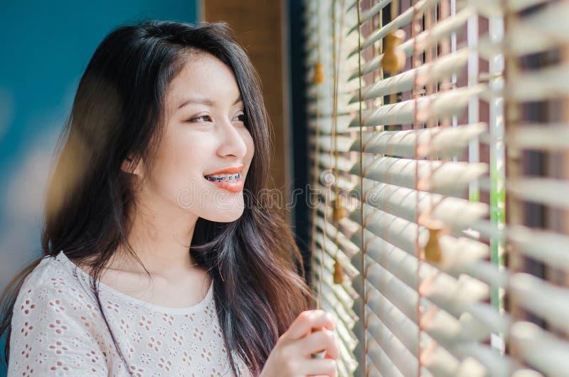 στάση γυναικών χαμόγελου η όμορφη κοντά στο παράθυρο εσωτερικό τα πρωινά είναι πολύ ευχάριστη στοκ εικόνα