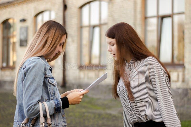 Στάση δύο η ελκυστική νέα φίλων κοντά στο πανεπιστήμιο και εξετάζει τα έγγραφα στοκ εικόνα