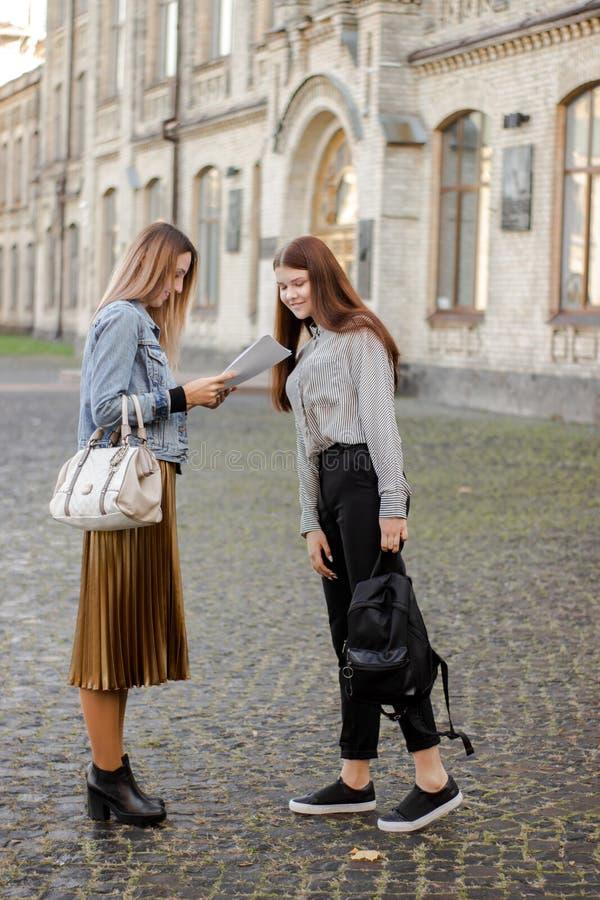 Στάση δύο η ευτυχής νέα φίλων κοντά στο πανεπιστήμιο και εξετάζει το έγγραφο στοκ φωτογραφία με δικαίωμα ελεύθερης χρήσης