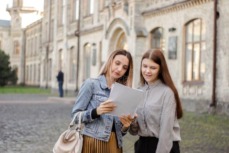 Στάση δύο η όμορφη κοριτσιών κοντά στο πανεπιστήμιο και εξετάζει το έγγραφο στοκ εικόνες με δικαίωμα ελεύθερης χρήσης