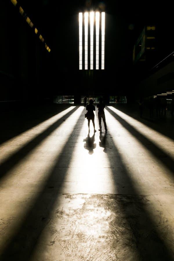 Στάση ζεύγους λαμβάνοντας υπόψη τα μπροστινά παράθυρα της αίθουσας στροβίλων του Tate Modern, Λονδίνο στοκ φωτογραφία με δικαίωμα ελεύθερης χρήσης