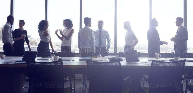 Στάση και συνομιλία Businesspeople πρίν συναντά στην αίθουσα συνεδριάσεων στοκ εικόνες
