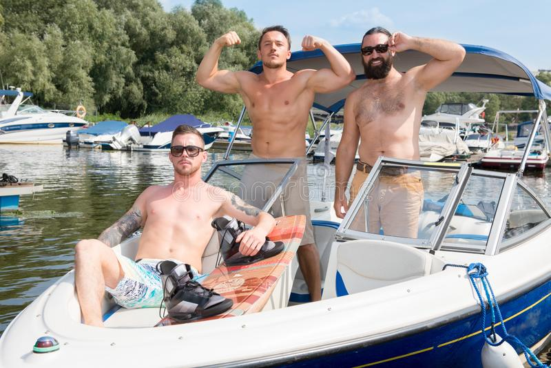 Στάση τριών τύπων σε μια βάρκα στην όχθη ποταμού στοκ εικόνες